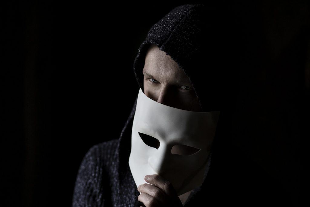 Man in hoodie peering over face mask